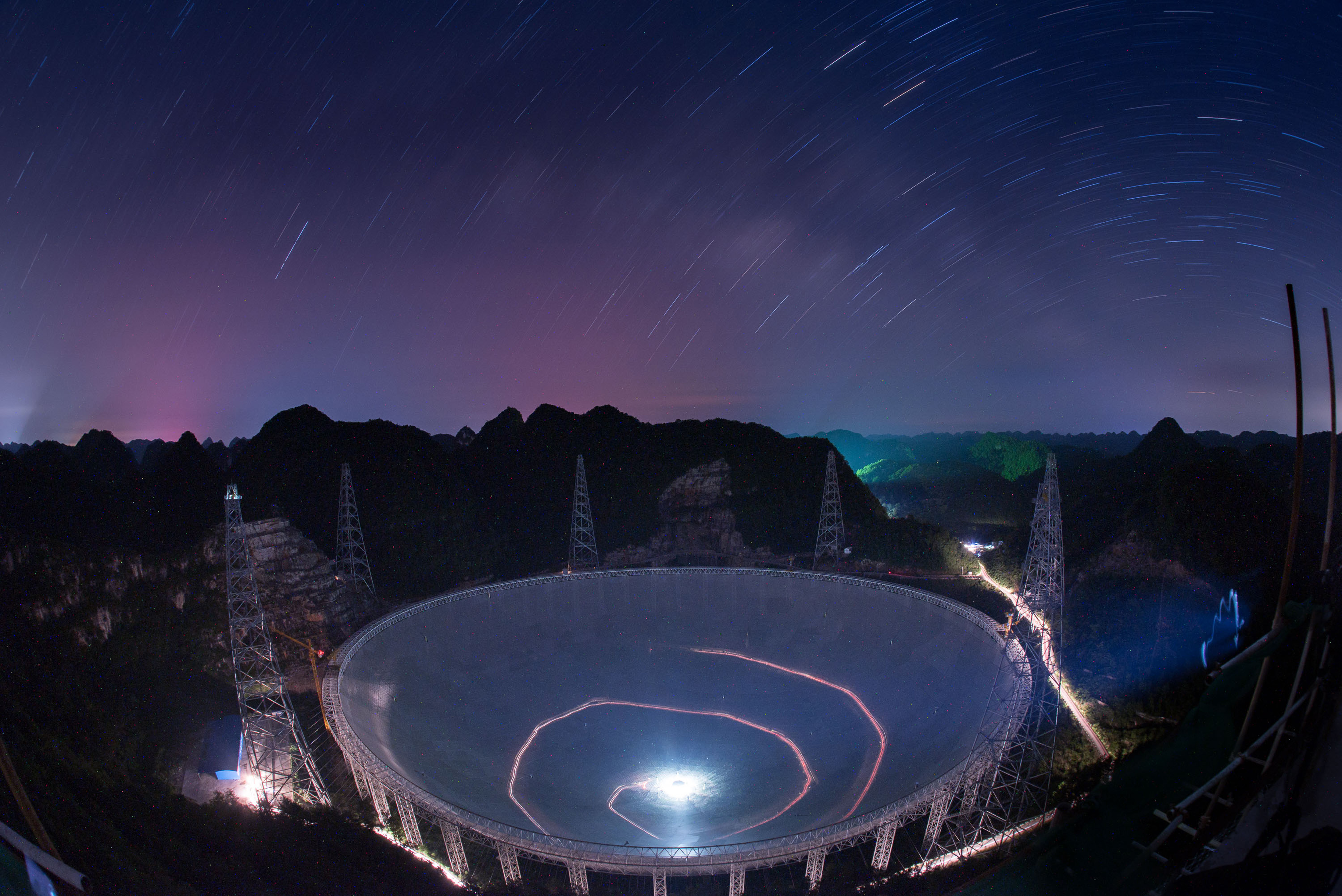In this photo released by China's Xinhua News Agency, a vehicle leaves light trails in a long exposure photo as it drives beneath the Five-hundred-meter Aperture Spherical Telescope (FAST) in Pingtang County in southwestern China's Guizhou Province Monday, June 27, 2016. Construction on the 500-meter (1600-feet) diameter radio telescope, which began in 2011, is nearing completion. (Liu Xu/Xinhua via AP)